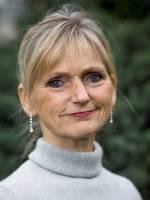 Portrett av Anne Lund mot grønn bakgrunn.
