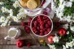 Bildet viser bringebær, epler, kjeks, en melkemugge og blomster på et bord