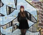 Julia standing in front of a graffiti wall.
